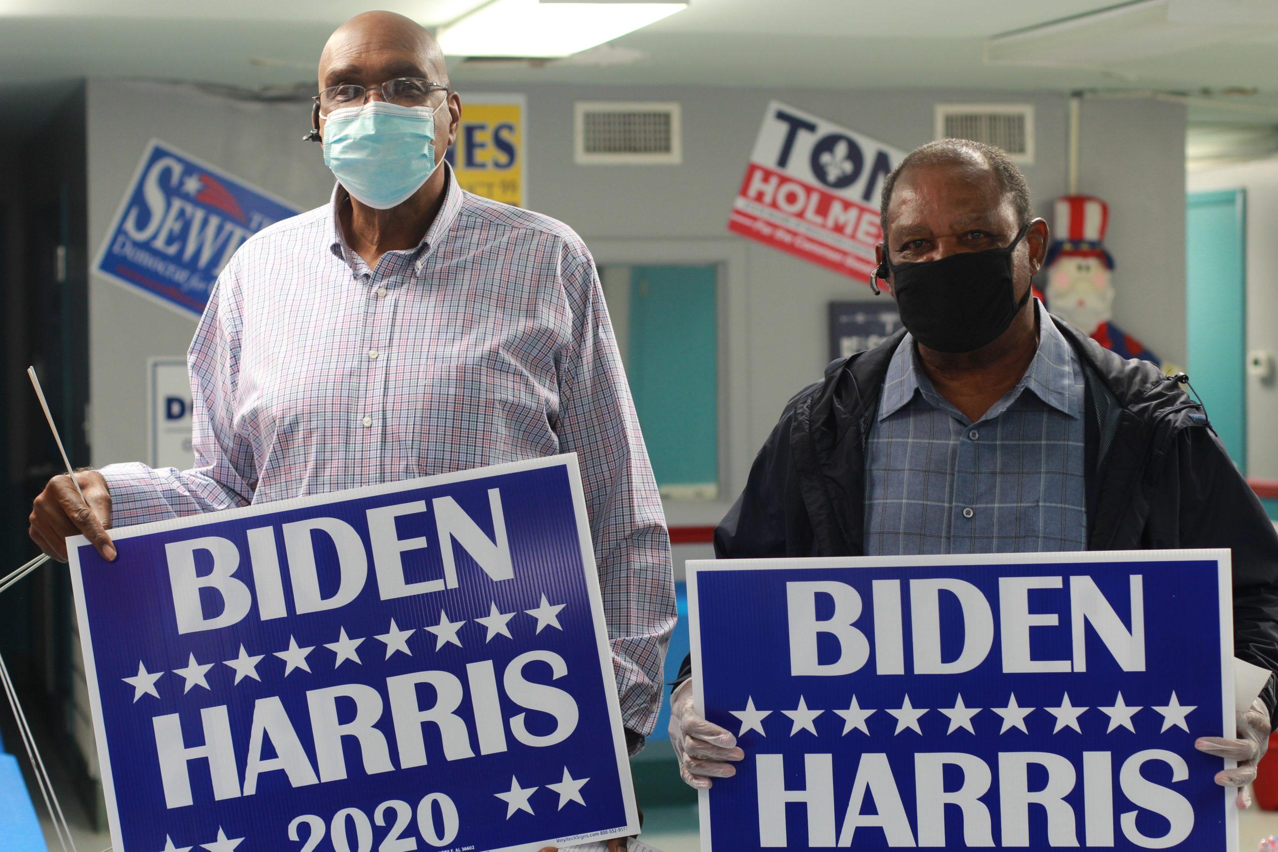 Men holding Biden Harris yard signs